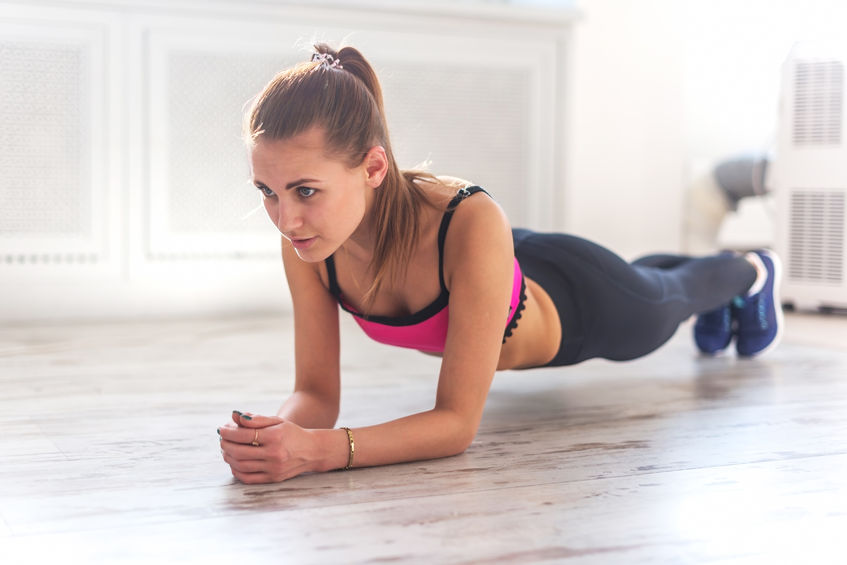 39238958 - slim fitnes young girl with ponytail doing planking exercise indoors at home gymnastics.