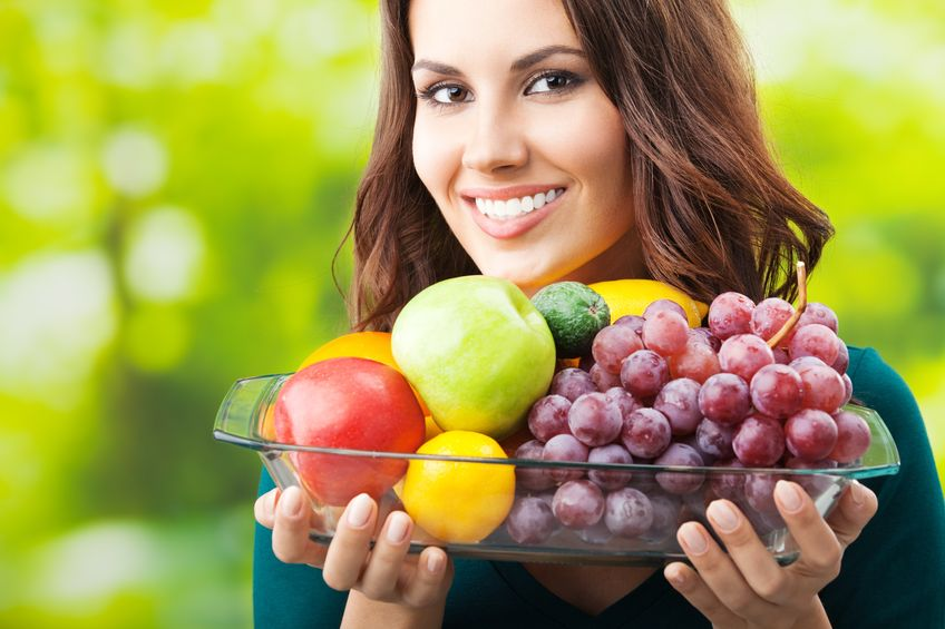 17888157 - young happy smiling woman with plate of fruits, outdoors