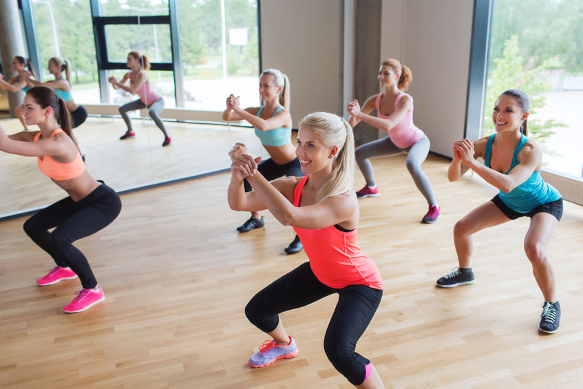 35289766 - fitness, sport, training, people and lifestyle concept - group of women making squats in gym