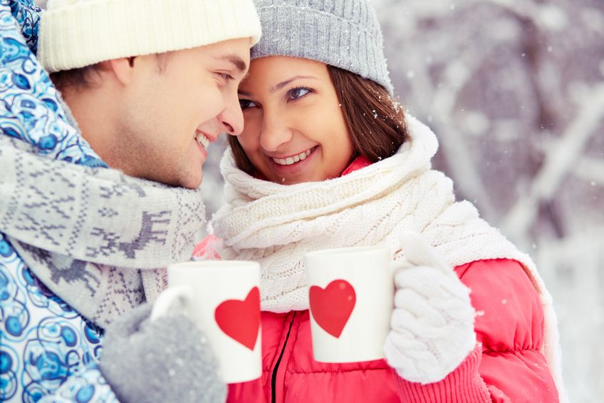 16964165 - portrait of happy young couple holding cups with red hearts in winter park