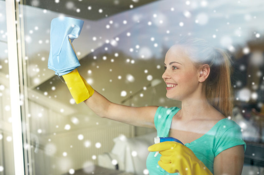 51385613 - people, housework and housekeeping concept - happy woman in gloves cleaning window with rag and cleanser spray at home over snow effect