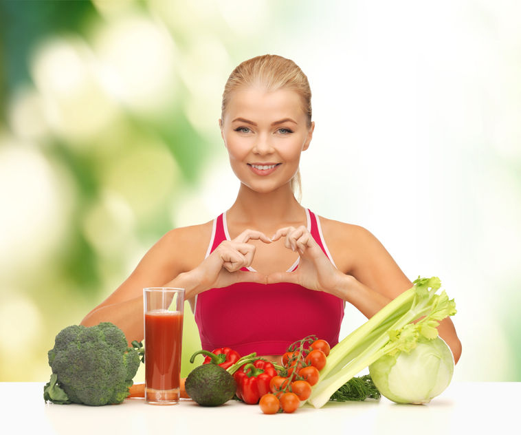 26175792 - fitness, diet and food concept - smiling woman with organic food showing heart shape with hands