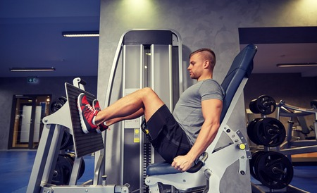 60804631 - sport, fitness, bodybuilding, lifestyle and people concept - man exercising and flexing leg muscles on gym machine