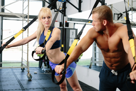 65948103 - photo of a muscular couple working out on suspension straps